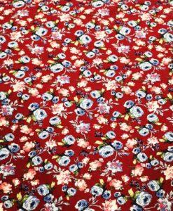 Blühender Baumwollstoff auf rotem Grund