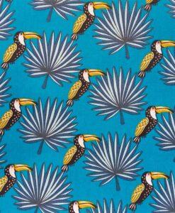 Tejido de algodón estampado con patrón de tucán, fondo azul.