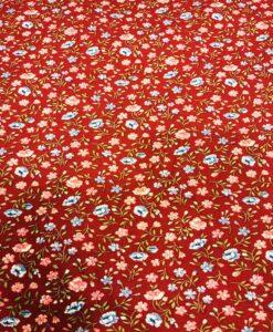 Kleine Blumen des Baumwollgewebes auf einem roten Hintergrund